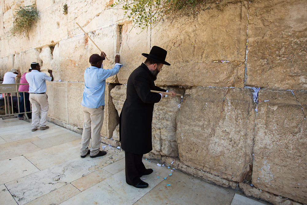 Western Wall Rabbi Shmuel Rabinowitz (C) and workers remove notes containing prayers and messages which were left by visitors, from the cracks between the stones of the Western Wall, Judaism's holiest prayer site, in the Old City of Jerusalem, Israel, on September 17, 2017. The clean-up which takes place ahead of the upcoming Jewish New Year Holiday, clears the wall's crevices and frees up space for more notes that people of all faiths slip between its stones, believing that requests deposited at the site are more likely to be heard by God.