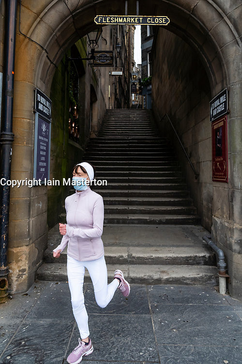 Female jogger wearing face mask running out of empty Fleshmarket Close during the coronavirus lockdown in Edinburgh Old Town, Scotland, UK