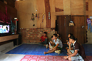 Penan watching television in wood and brick built municipal longhouse. Kelabit native people facing a mounting threat to lose their traditional lands, ancestral burial grounds, culture and habitat, once the hydro-electric dam project floods their lands. Limbang, Sarawak Borneo..The Limbang valley including Long Napir, a cluster of four settlements of Penan and Kelabit people, is threatened by a new hydro-electric project which will flood the entire area, displacing thousands of native people. The Murum Hydro-electric project already underway affecting the Rejang region, will displace over 24,000 Dayak native residents, destroying their longhouses and forest habitat. The dam site is located on the Murum River, in the uppermost part of the Rajang River basin, 200km from Bintulu...Borneo native peoples and their rainforest habitat revisited two decades later: 1989/1991-2012. ..Sarawak's primary rainforests have been systematically logged over decades, threatening the sustainable lifestyle of its indigenous peoples who relied on nomadic hunter-gathering and rotational slash & burn cultivation of small areas of forest to survive. Now only a few areas of pristine rainforest remain; for the Dayaks and Penan this spells disaster, a rapidly disappearing way of life, forced re-settlement, many becoming wage-slaves. Large and medium size tree trunks have been sawn down and dragged out by bulldozers, leaving destruction in their midst, and for the most part a primary rainforest ecosystem beyond repair. Nowadays palm oil plantations and hydro-electric dam projects cover hundreds of thousands of hectares of what was the world's oldest rainforest ecosystem which had some of the highest rates of flora and fauna endemism, species found there and nowhere else on Earth, and this deforestation has done irreparable ecological damage to that region.