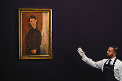 © Licensed to London News Pictures. 19/06/2019. LONDON, UK. A technician presents ''Jeune Homme Assis, Les Mains Croisées Sur Les Genoux'' by Amedeo Modigliani, (Est. £16,000,000 - 24,000,000) which sold for a hammer price of £16,000,000 at Sotheby's Impressionist & Modern art evening sale in New Bond Street. This is the first major evening sale to take place after Sotheby's agreed to a takeover by media and telecoms billionaire Patrick Drahi in a deal valued at $3.7bn (£2.9bn).  The big five global auction houses (Sotheby's, Christie's, Bonhams, Phillips and China Guardian Auctions) will now be held privately.  Francois Pinault, another French billionaire, owns Sotheby's traditional rival Christie's.   Photo credit: Stephen Chung/LNP