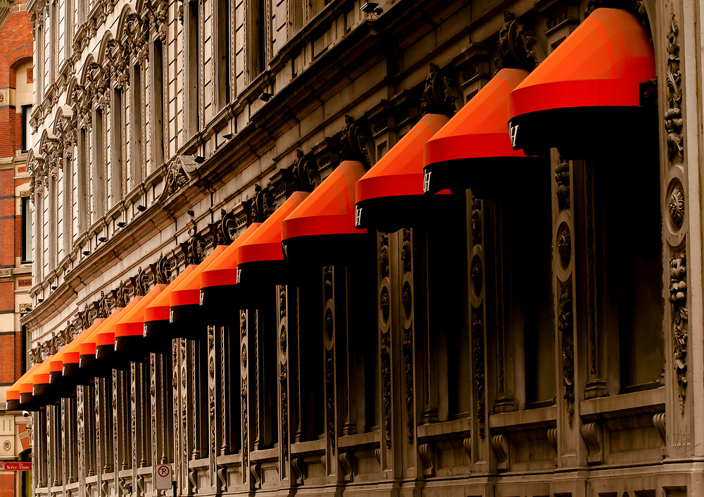 Rue Saint Jacques/Saint Jean Hotel Montreal               <br /> About the Subject: Old Montreal (Vieux, Montréal) has a wealth of highly ornate, historical architecture and detail. Narrow, congested streets make photography challenging. <br /> <br /> About the Photo: Layers of detailed stonework, windows and designs are accentuated here with dramatic awnings and punctuated by an incongruous 'No Parking' sign. Strong vertical lines, including those of a second, brick, building give a sense of substance and mass while the orange and black diagonal provides drama. Shot from across the street in order to maintain perspective and, at the same time, capture the rows of repetitive elements.