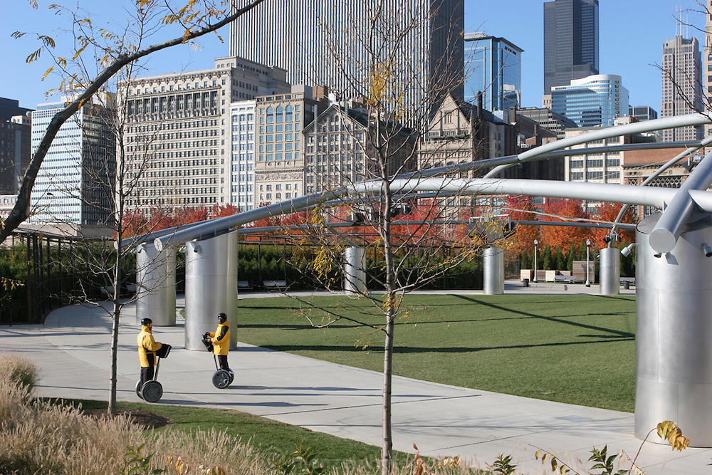 Two riders on Segway motorized transports pass near the Frank Gehry-designed Jay Pritzker Pavilion trellis structure in Millennium Park, Chicago, Il. USA .