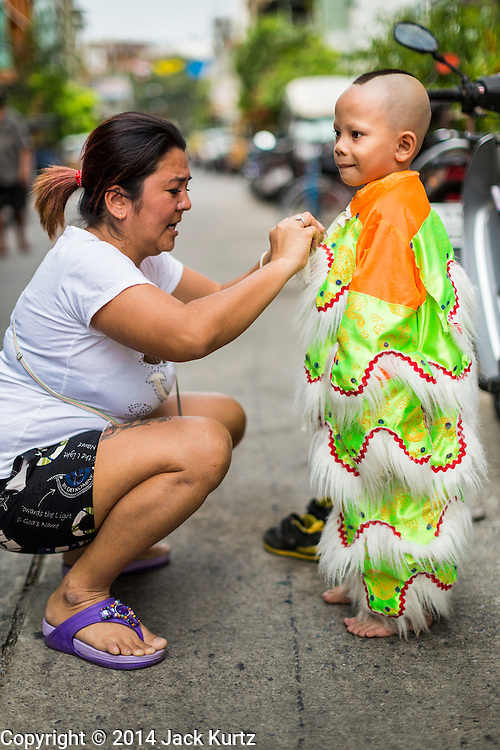 24 SEPTEMBER 2014 - BANGKOK, THAILAND: A member of a traditional dance troupe gets into his costume before the Vegetarian Festival parade in Bangkok. The Vegetarian Festival is celebrated throughout Thailand. It is the Thai version of the The Nine Emperor Gods Festival, a nine-day Taoist celebration beginning on the eve of 9th lunar month of the Chinese calendar. During a period of nine days, those who are participating in the festival dress all in white and abstain from eating meat, poultry, seafood, and dairy products. Vendors and proprietors of restaurants indicate that vegetarian food is for sale by putting a yellow flag out with Thai characters for meatless written on it in red.    PHOTO BY JACK KURTZ