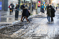 © Licensed to London News Pictures. 21/01/2020. London, UK. Members of public are seen jumping over the mud outside Southwark Tube station after flooding from burst pipe. Photo credit: Dinendra Haria/LNP