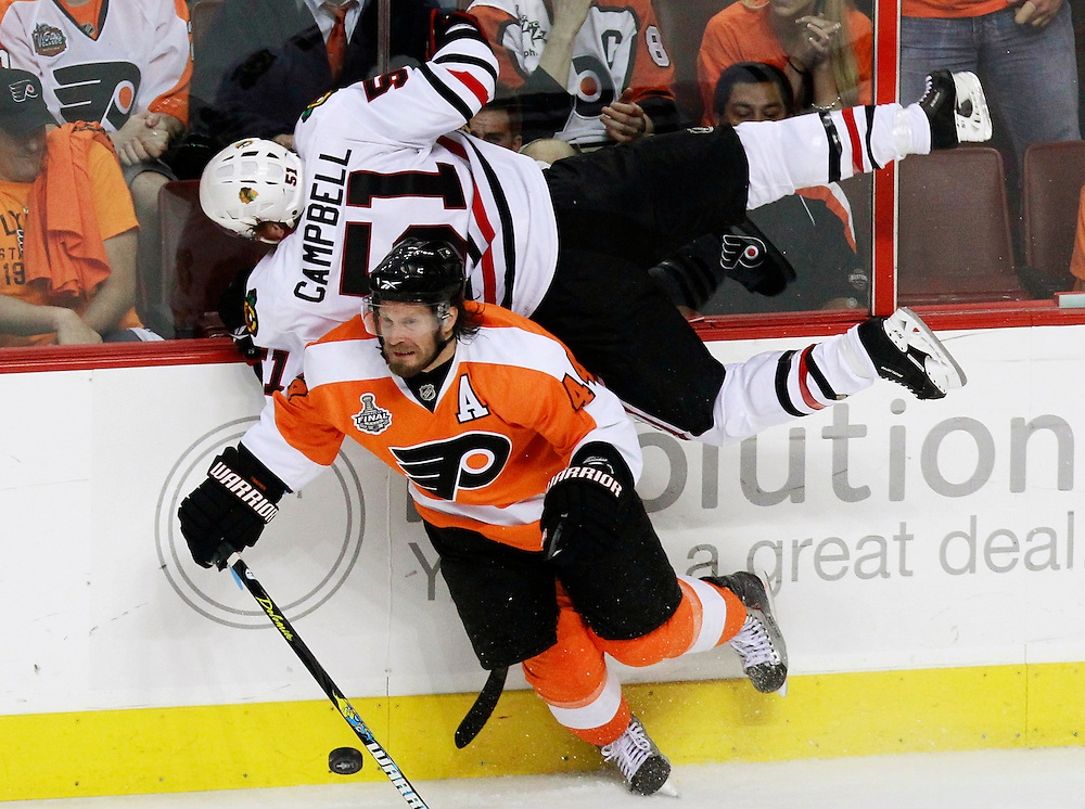 Philadelphia Flyers' Kimmo Timonen (BOTTOM) checks Chicago Blackhawks' Brian Campbell during the first period in Game 4 of the NHL Stanley Cup final hockey series in Philadelphia, June 4, 2010.   REUTERS/Jim Young