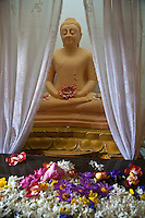 Buddha Image and floral offerings at  The Temple of the Sacred Tooth Relic - a Buddhist temple in Kandy, Sri Lanka and UNESCO World Heritage site.