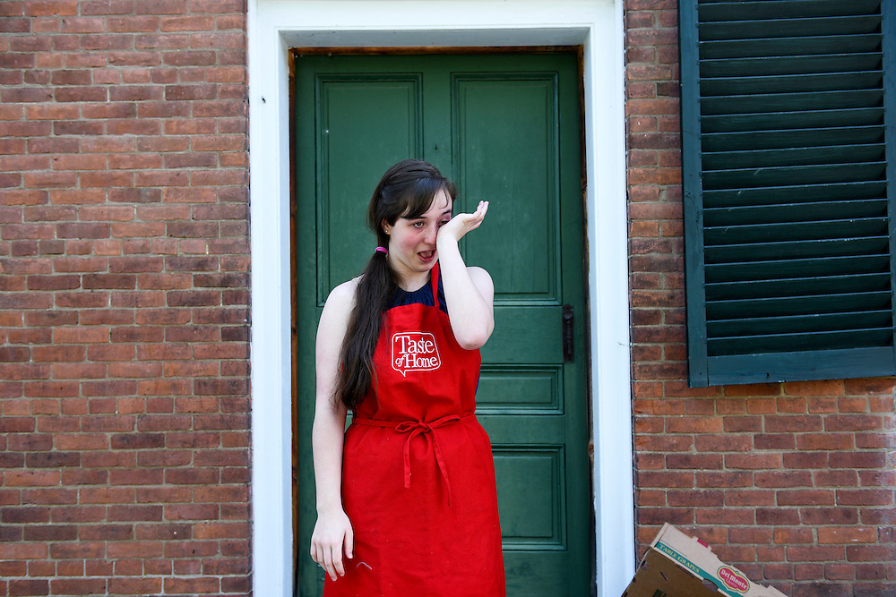Virginia Drye, 16, stepped onto the porch of the Blow-Me-Down Grange in Plainfield, N.H. to rest her teary eyes after cutting onions Wednesday, May 27, 2015 for the monthly Plainfield, Cornish senior luncheon. Drye is a member of Covered Bridge 4H, and the group cooks and serves the luncheon once a year. (Valley News - James M. Patterson)<br /> Copyright © Valley News. May not be reprinted or used online without permission. Send requests to permission@vnews.com.