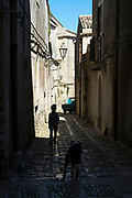 Street scene of boy and dog in cobble stones alleyway in Erice, Sicily, Italy