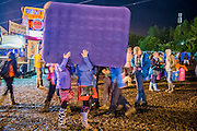 Late arrivals (it is nearly 2 in the morning) have just purchased and inflatable bed but are struggling to get it home. The 2015 Glastonbury Festival, Worthy Farm, Glastonbury.