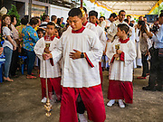 18 SEPTEMBER 2016 - BANGKOK, THAILAND:  Alter servers lead a procession into the sanctuary for the 100th anniversary mass for the sanctuary at Santa Cruz Catholic Church. Santa Cruz Church was establised in 1769 to serve Portuguese soldiers in the employ of King Taksin, who reestablished the Siamese (Thai) empire after the Burmese sacked the ancient Siamese capital of Ayutthaya. The church was one of the first Catholic churches in Bangkok and is one of the most historic Catholic churches in Thailand. The first sanctuary was a simple wood and thatch structure and burned down in the 1800s. The church is in its third sanctuary and was designed in a Renaissance / Neo-Classical style. It was consecrated in September, 1916. The church, located on the Chao Phraya River, serves as a landmark for central Bangkok.      PHOTO BY JACK KURTZ
