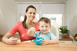 Portrait of mother and son in kitchen, smiling