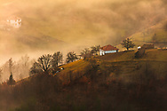 Houses of a small village scattered around Mountain hills at rainy morning