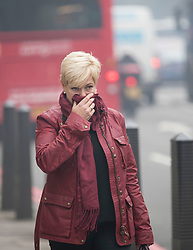 © Licensed to London News Pictures. 14/11/2017. London, UK. A woman covers her mouth and nose as smoke is seen rising from a tower block near Edgeware Road tube. The area filled with acrid smelling smoke until the Fire Brigade arrived.Photo credit: Peter Macdiarmid/LNP