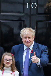 © Licensed to London News Pictures. 28/10/2019. London, UK. The Prime Minister BORIS JOHNSON on the steps of No 10 Downing Street with 10 years old Maisie Gardner after purchasing a poppy. Later today MPs will vote on BORIS JOHNSON's motion on a general election on  December 2019. Photo credit: Dinendra Haria/LNP