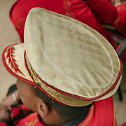 The golden hat of a musician. The band follows the wedding party across town.