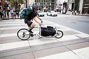 In San Francisco rijdt een fietskoerier bij het Financial district. De Amerikaanse stad San Francisco aan de westkust is een van de grootste steden in Amerika en kenmerkt zich door de steile heuvels in de stad. Ondanks de heuvels wordt er steeds meer gefietst in de stad.<br /> <br /> Cyclists in San Francisco. The US city of San Francisco on the west coast is one of the largest cities in America and is characterized by the steep hills in the city. Despite the hills more and more people cycle.