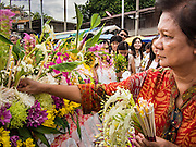 """22 JULY 2013 - PHRA PHUTTHABAT, THAILAND:  A woman places flowers on the truck carrying the Buddha during the Tak Bat Dok Mai at Wat Phra Phutthabat in Saraburi province of Thailand, Monday, July 22. Wat Phra Phutthabat is famous for the way it marks the beginning of Vassa, the three-month annual retreat observed by Theravada monks and nuns. The temple is highly revered in Thailand because it houses a footstep of the Buddha. On the first day of Vassa (or Buddhist Lent) people come to the temple to """"make merit"""" and present the monks there with dancing lady ginger flowers, which only bloom in the weeks leading up Vassa. They also present monks with candles and wash their feet. During Vassa, monks and nuns remain inside monasteries and temple grounds, devoting their time to intensive meditation and study. Laypeople support the monastic sangha by bringing food, candles and other offerings to temples. Laypeople also often observe Vassa by giving up something, such as smoking or eating meat. For this reason, westerners sometimes call Vassa the """"Buddhist Lent.""""    PHOTO BY JACK KURTZ"""