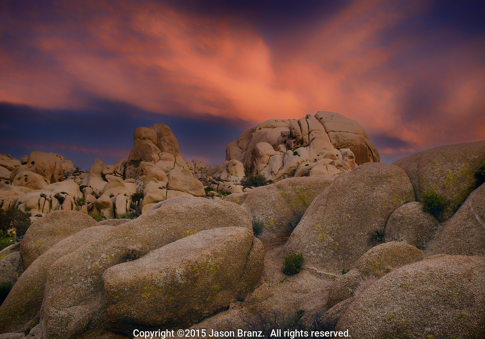 Dramatic sunset light on high clouds over granite boulders at Joshua Tree National Park, California.