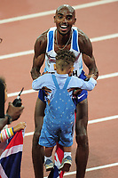 Athletics - 2017 IAAF London World Athletics Championships - Day One<br /> <br /> Mens 10,000m Mens Final<br /> <br /> Mohamed Farah (Great Britain) picks up one of his sons after winning the race, at the London Stadium.<br /> <br /> COLORSPORT/ANDREW COWIE