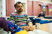 A Polish man sitting in the dining room of Slough Homeless our concern (SHOC) A local homeless charity helping the homeless and vulnerable in Slough. Berkshire, UK.