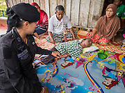17 JUNE 2015 - RANGAE, NARATHIWAT, THAILAND:  Thai Army Ranger 2nd Lt MONTHA SOMPIASERT, left, talks to a Thai Muslim family in their home. Their son had polio as a child and is now disabled. The Rangers bring them food and perform wellness checks as a part of the Rangers' outreach program. There are 5 platoons of women Rangers serving in Thailand's restive Deep South. They generally perform security missions at large public events and do public outreach missions, like home wellness checks and delivering food and medicine into rural communities. The medics frequently work in civilian clothes because the Rangers found people are more relaxed around them when they're in civilian clothes. About 6,000 people have been killed in sectarian violence in Thailand's three southern provinces of Narathiwat, Pattani and Yala since a Muslim insurgency started in 2004. Attacks usually spike during religious holidays. Insurgents are fighting for more autonomy from the central government in Bangkok.    PHOTO BY JACK KURTZ