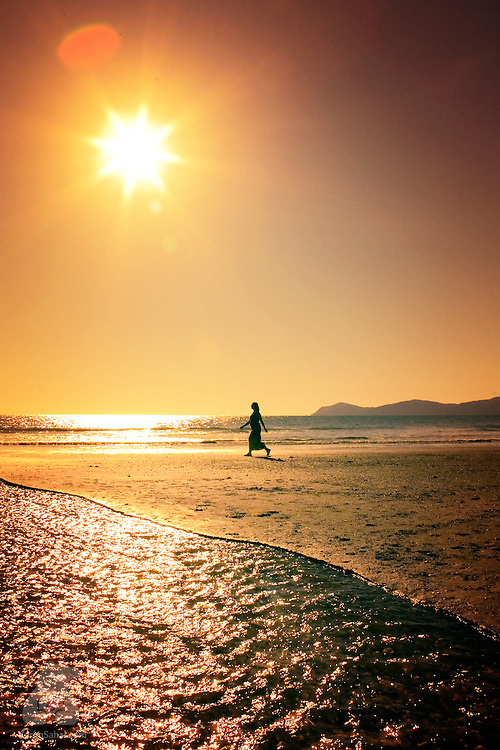 A woman walking on the beach appears as a silhouette against the late afternoon sky. Kapiti Coast, Wellington, New Zealand.