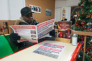 A man reading a political promotional newspaper titled Labour Today with the headline Vote Helen Hayes Vote Remain in the Express Cafe in Brixton Village on the 11th December 2019 in London in the United Kingdom.  Helen Hayes is a British Labour Party politician who has been the Member of Parliament for Dulwich and West Norwood since the May 2015 general election.