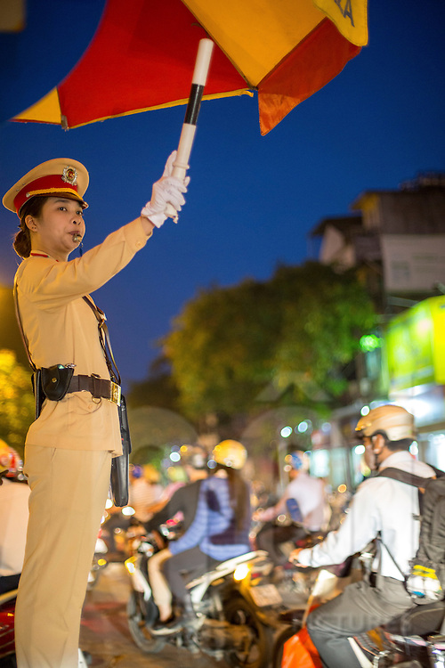 A police woman controls the traffic along Cat Linh Street in Hanoi, Vietnam, Southeast Asia