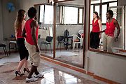 Cuba is the spiritual home of Salsa, and many people come to the Havana to learn the dance. Here a female tourist takes classes with a local Cuban man, in a small dance studio on the roof of a house.