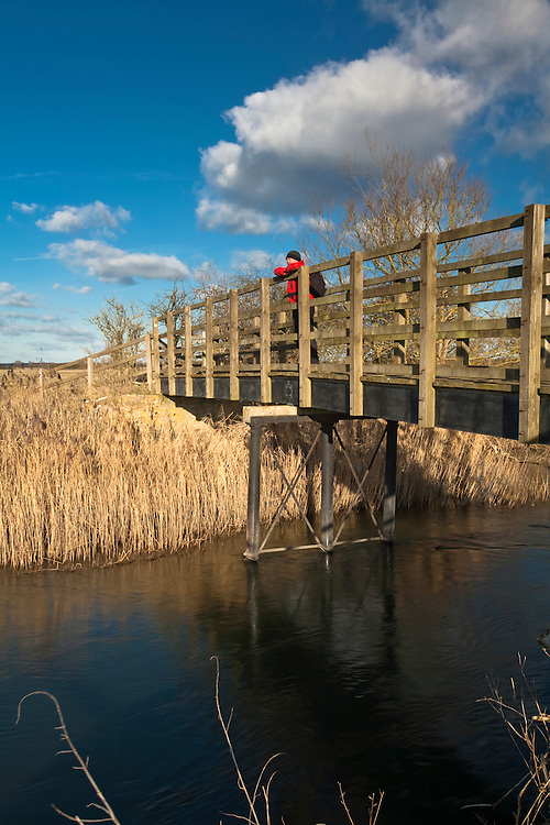 Walker crossing a wooden footbridge over the upper reaches of the River Thames near Cricklade, Wiltshire, Uk
