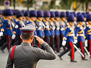 02 DECEMBER 2014 - BANGKOK, THAILAND: A Thai policeman salutes as military units march past him in the annual Trooping of the Colors parade on Sanam Luang in Bangkok. The Thai Royal Guards parade, also known as Trooping of the Colors, occurs every December 2 in celebration of the birthday of Bhumibol Adulyadej, the King of Thailand. The Royal Guards of the Royal Thai Armed Forces perform a military parade and pledge loyalty to the monarch. Historically, the venue has been the Royal Plaza in front of the Dusit Palace and the Ananta Samakhom Throne Hall. This year it was held on Sanam Luang in front of the Grand Palace.    PHOTO BY JACK KURTZ