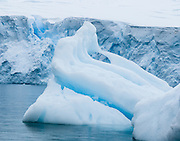 A tidewater glacier on the continent of Antarctica calves icebergs into Neko Harbor (an inlet of the Southern Ocean), at Graham Land, the north portion of the Antarctic Peninsula.
