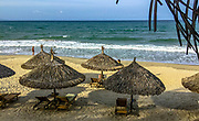 An Bang Beach Umbrella huts and lounge chairs with the Ocean surf coming in.