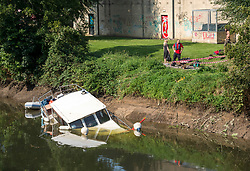 "© Licensed to London News Pictures; 16/09/2020; Bath, UK. The canal boat ""Pollyanna"" is seen partly submerged on the river Avon in Bath. Canal boats were evacuated and some boats sunk on the river Avon at Twerton after the sluice gates failed yesterday evening (15 September) and the water level dropped dramatically. The Fire Service assisted. The Canal and River Trust have issued a statement saying a drop in water level on the River Avon was caused by a failure of the Environment Agency's sluice gates and that the sudden and dramatic drop in levels meant that it was impossible to give warning to the boaters. The Canal and River Trust say they understand the difficulties faced by the EA in repairing the sluice and this is the second time this has happened, so they are looking to the EA to find a solution as a matter of urgency.  Photo credit: Simon Chapman/LNP."