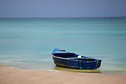 A blue boat is anchored on the shore of a beautiful beach in the Dominican Republic