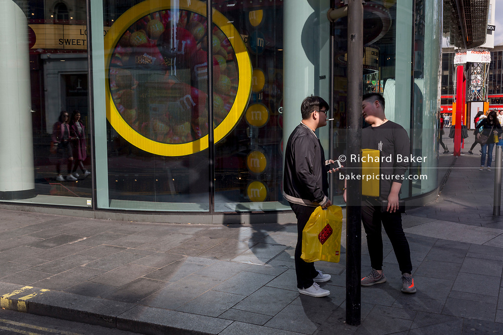 Two men of Chinese appearance stand outside the M&M shop near Chinatown, on 28th March, 2017, in Leicester Square, London, England.