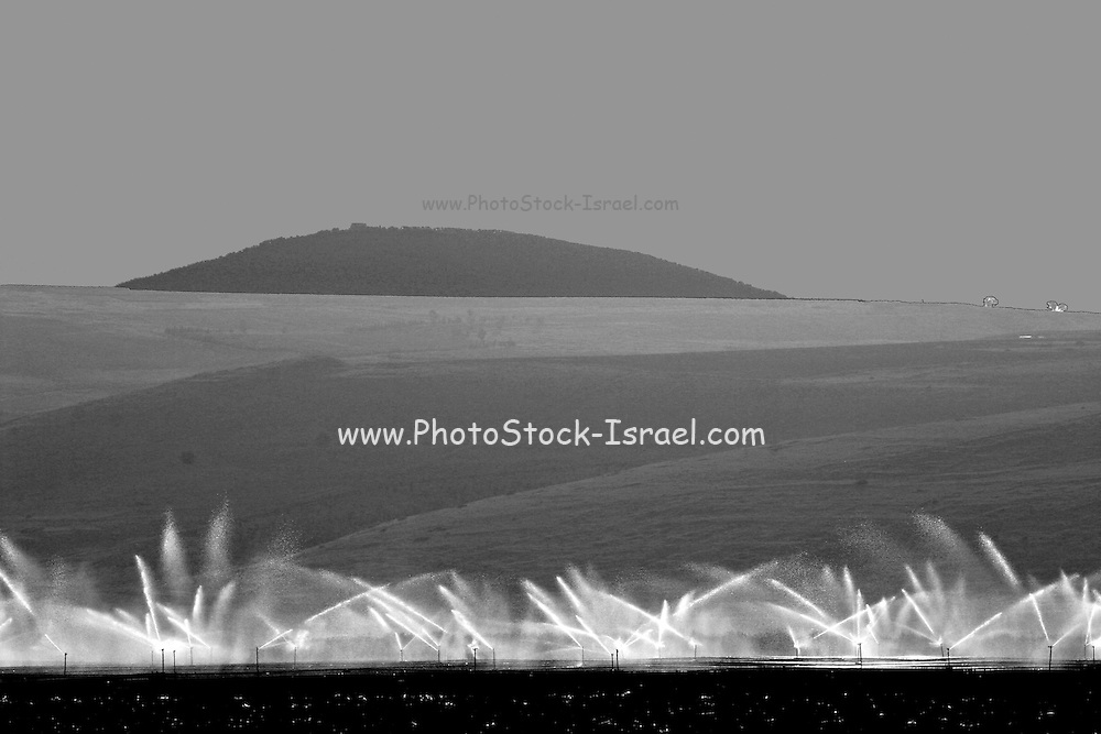 Israel, Jezreel Valley, Galilee irrigation of agricultural fields mount Tabor in the background , Jezreel