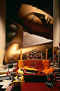 A monk meditates in Sing Buri, Thailand under the watchful eye of a 52-meter long buddah at wat pra nan chaksri.
