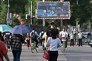 """Pedestrians who jay walk or who cross when there is a red light can be fined 20 yuan after they do this three times. They are named and shamed after the offence. An image of their face and name appears of the video screen for all to see. This is part of a new control with face recognition camera software installatioin at traffic lights. Offences and misdemeanours such as these can contribute to a citizen's social credit rating. They lose points for a traffic ticket but gain points for an """"exemplary city level heroic act"""". A poor social credit score can lead to bans from travel, certain schools, luxury hotels, government positions and even dating apps. Traffic lights at crossroads. Beijing outskirts. China"""