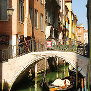 Gondola under bridge in venetian canal