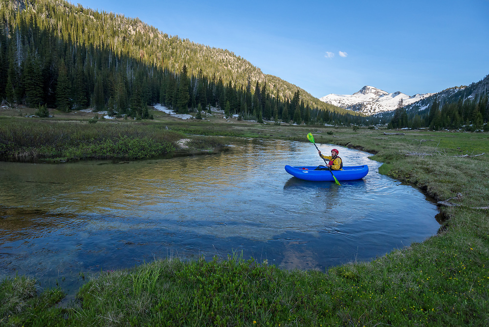 Paddling an inflatable kayak on a stream through a subalpine meadow in Oregon's Eagle Cap Wilderness.