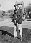 E.O.H. Self-Portrait, standing taking a photograph outdoors, c1924