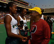 Shalonda Solomon (left) and Chanda Picott of Long Beach Poly High (Calif.) are congratulated by Bill Cosby after setting a national high school record of 44.50 seconds in the 110th Penn Relays at  Franklin Field on Friday, April 23, 2004 in Philadelphia.
