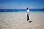Traveler surveying the scene at Lalomanu Beach, near the eastern tip of Upolu, Western Samoa.