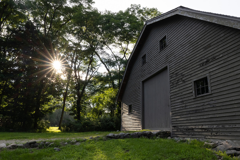 Summertime sunshine glowing on the facade of an old barn within Minuteman National Park.