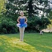 Girl (8-10) in ballerina costume standing in yard with cat, portrait