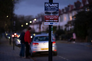 A pair of eyes watch over a darkening suburban residential street, on a sign that warns fly-tippers not to dump rubbish on this street in south London, on 4th November 2020, in London, England.