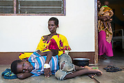 A grandmother mother and her grandson Imamsit in the shade and cool air outside the children's ward of St Walburg's Hospital, Nyangao. Lindi Region, Tanzania.