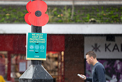 © Licensed to London News Pictures. 03/11/2020. St Helens, UK. A man walks by a poppy for remembrance beside a covid sign as people brave the rain in St Helens to do some shopping. Photo credit: Kerry Elsworth/LNP