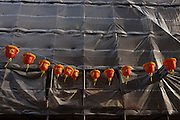 Chinese Moon Festival lanterns hang high above street level, attached to construction site sheeting.
